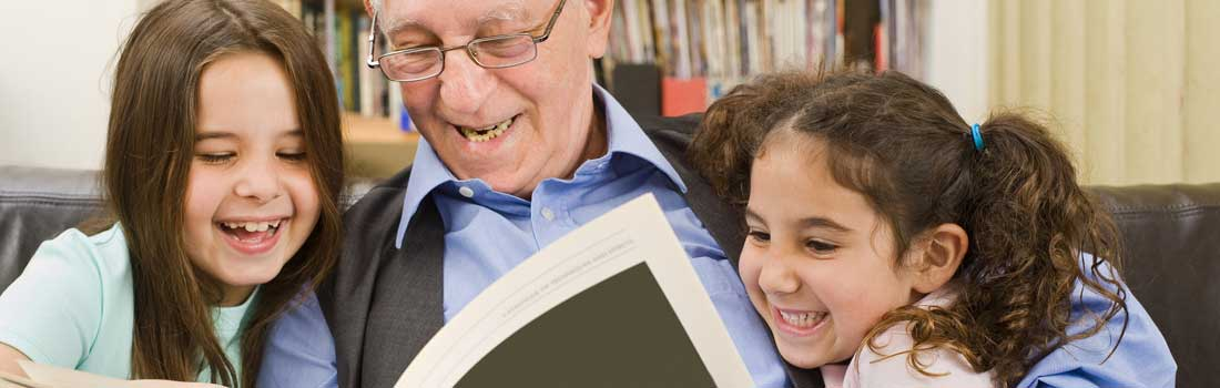 senior reading book to young girls