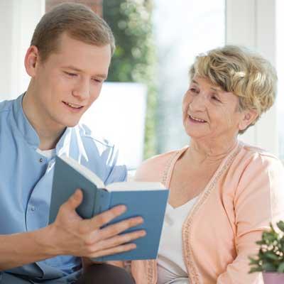 man reading book to elderly woman