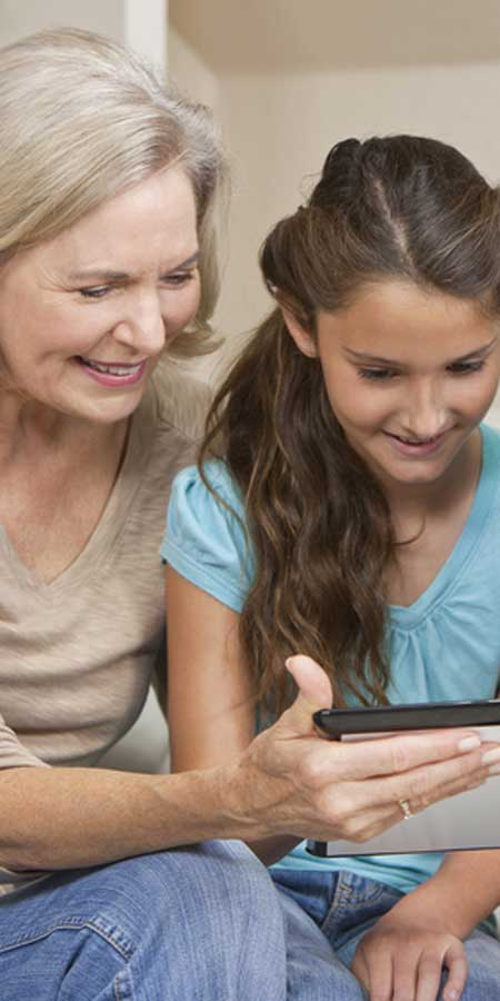 granddaughter and grandmother using tablet